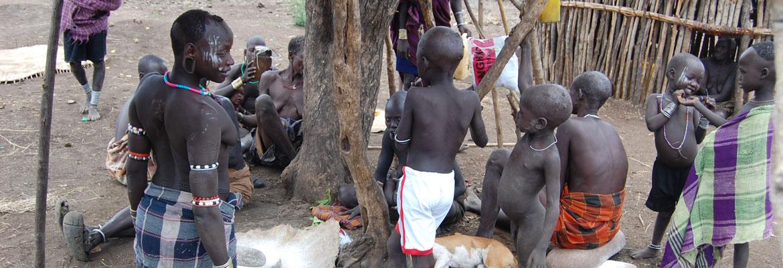 Vrouwen en kinderen bij malen van sorghum in Miro Beh Village